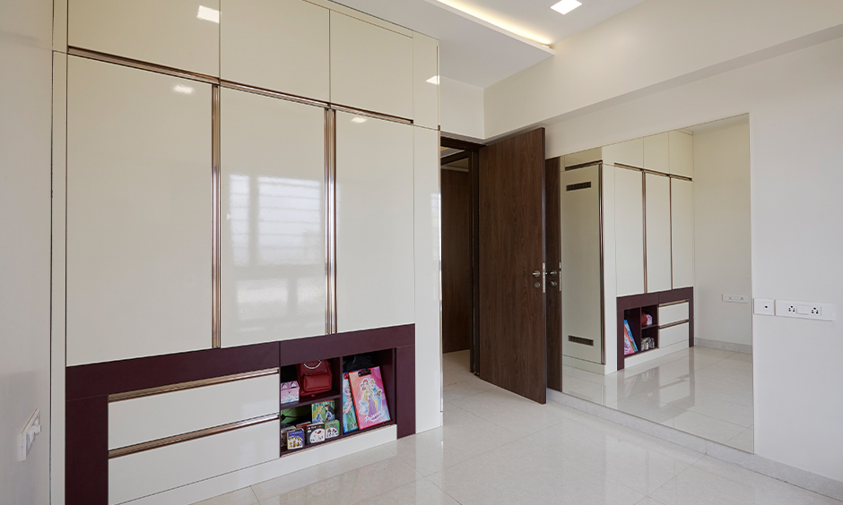 Big mirror and floor-to-ceiling wooden wardrobe in the Kids bedroom bring aesthetic, home interiors in Mumbai.