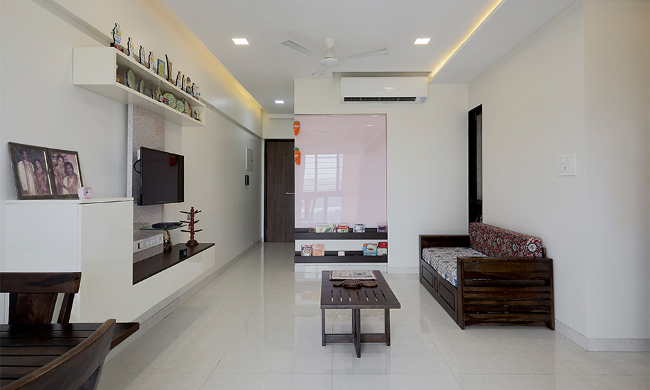 White living room designed with a TV unit, centre table and ceiling lights looks minimalist, home interior in Mumbai.