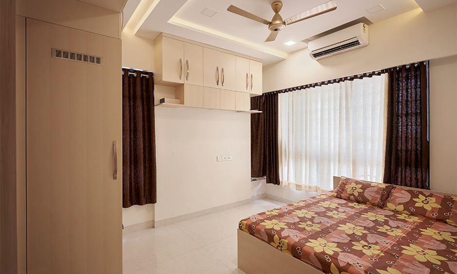Master bedroom design with a wall-mounted storage unit and ceiling light elegant look, a home interior company in Mumbai.