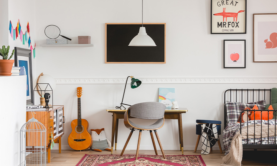 A room decorated in artist style with paper wall art, poster frames, and study table is modern room decoration for boys.