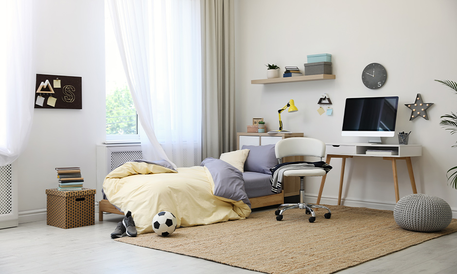 A room decorated with earthy rugs, storage boxes, and wall art is how to decorate boys room in minimalistic.