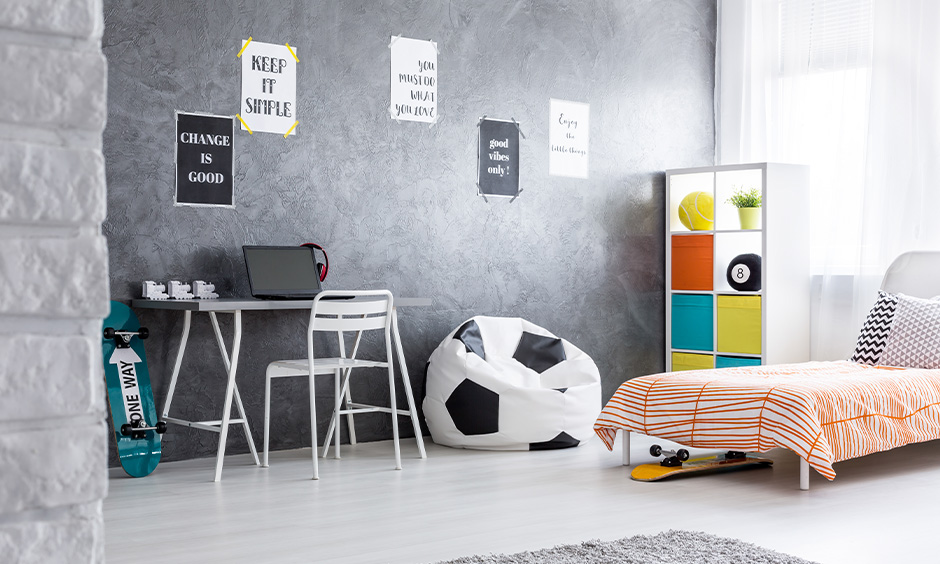 The room decorated with a basketball bean bag, cabinet, and quotes wallpaper on the wall are boys room decor ideas.