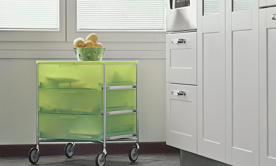 Metal kitchen island cart with pull out storage and items like cookbooks, cutlery and plates