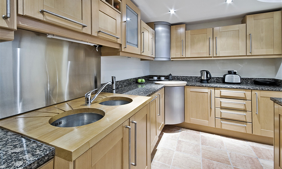 Double bowl kitchen sink with drainboard with light oak wood cabinets