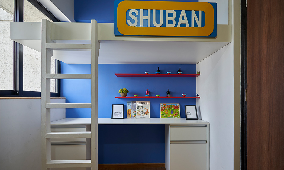 The small kid's bedroom has a bunk bed with a study table in minimal design in dombivil mumbai