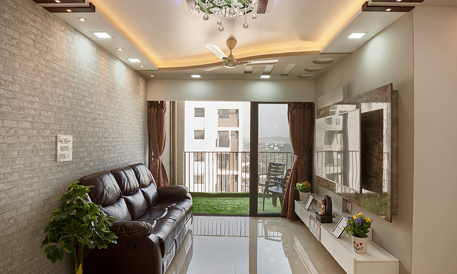 Modern eclectic style living room design in in dombivil mumbai with a TV unit, sofa, brick cladding and ceiling light looks elegant.