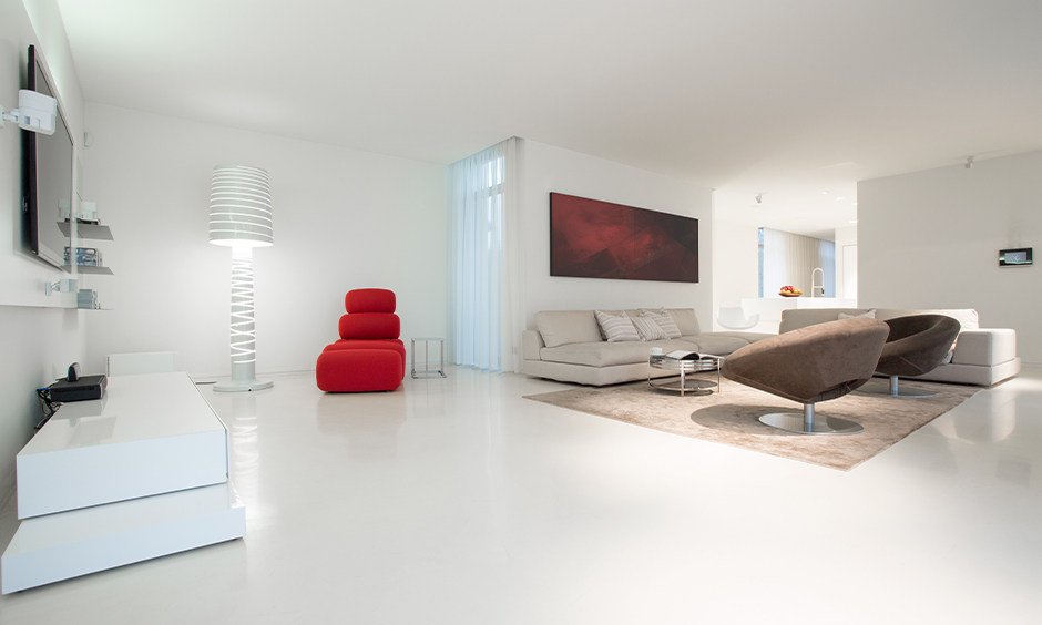 White living room with white marble flooring designed in minimal and colourful types of furniture looks splendid.
