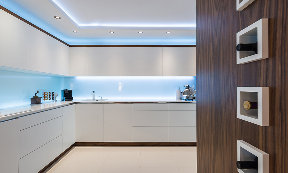 White kitchen with blue-toned lights under white cabinets looks refreshing is the led lights for kitchen cabinets.