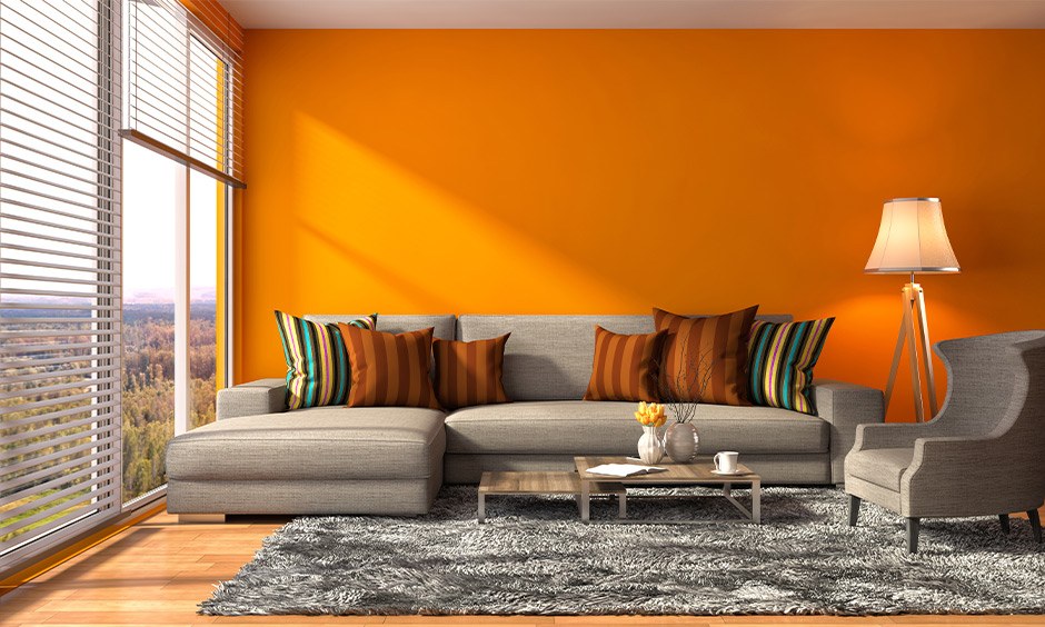 Living room orange wall analogous color scheme brings sunset vibe to the area.
