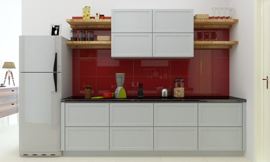 Modern kitchen wall tiles design in India, one-wall kitchen has minimal red coloured backsplash tiles and white cabinets.