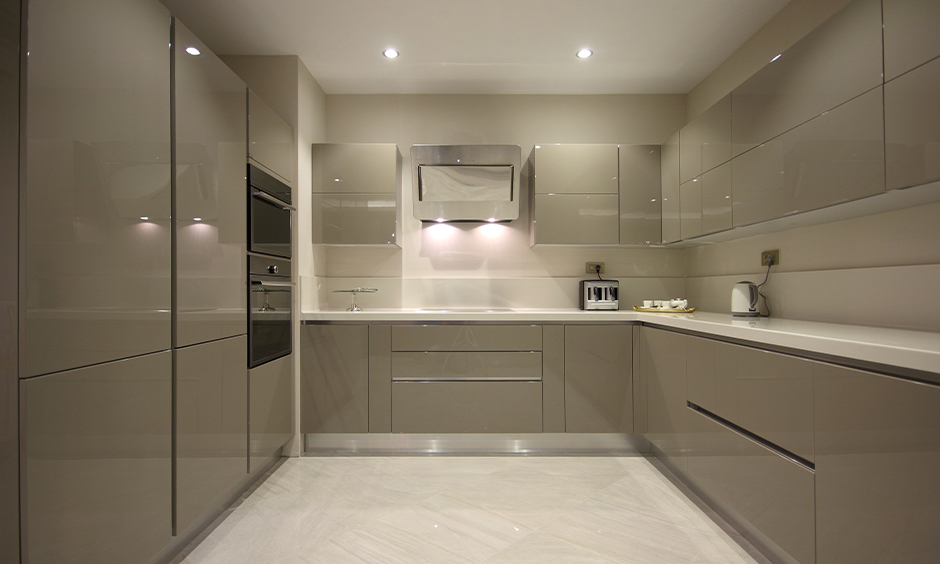 U-shaped kitchen has high gloss kitchen cabinets colours in the light grey aesthetic look.