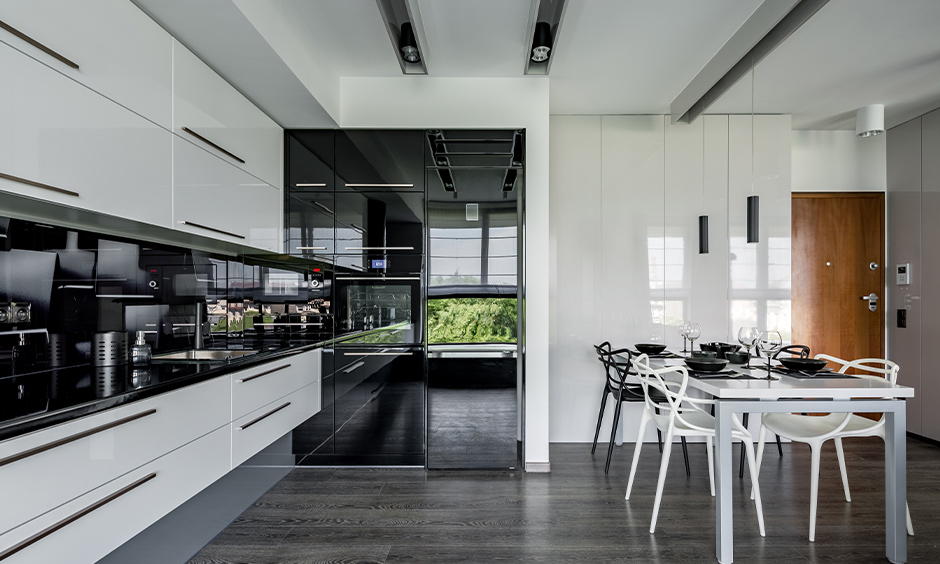 Kitchen cum dining area with high gloss laminate kitchen cabinets in minimal white and black design.
