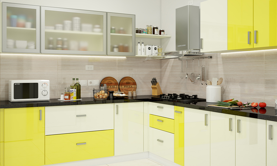 L-shaped kitchen with modern high gloss kitchen cabinets in yellow and white colour combination looks splendid.