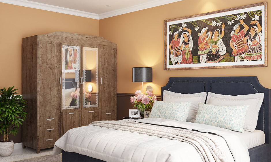 An old wardrobe decorated with mirrors on the door in the master bedroom is functional and contemporary almirah decoration.