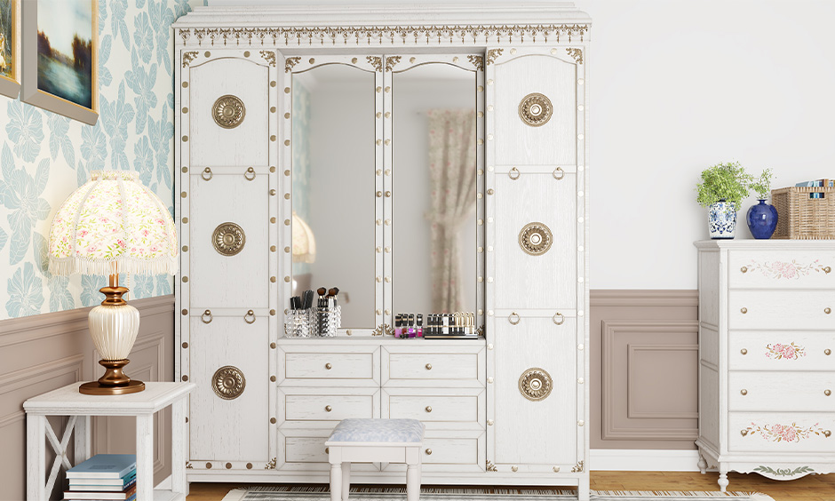 The old white wardrobe/almirah  decorated with vintage doorknobs look beautiful in the bedroom.