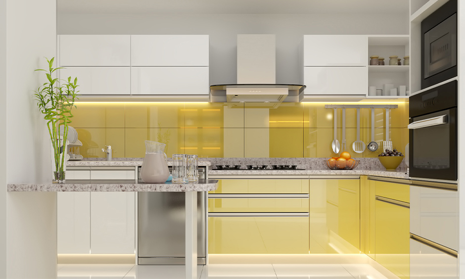 Grey and yellow kitchen with breakfast counter and cabinet lighting look classy.