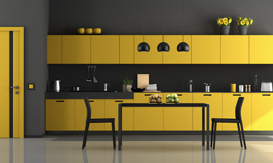 The yellow and black modular kitchen cum dining area has a black dining table that brings in fresh bursts of colour.