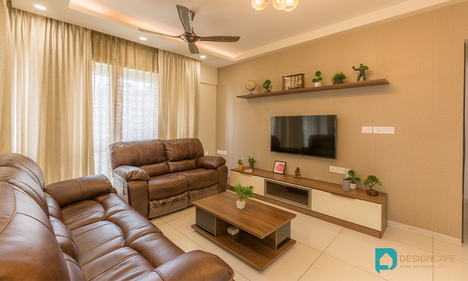 The earthy colour living room designed with a tv unit, sofa and centre table, interior designers in Whitefield.