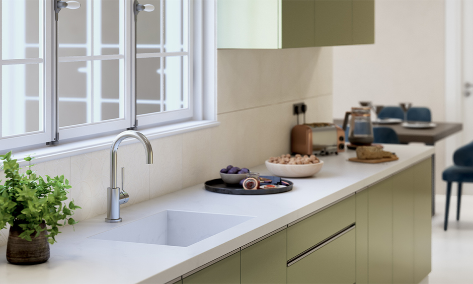 Integrated single-bowl white marble kitchen sink with olive green PVC cabinet below looks aesthetic.