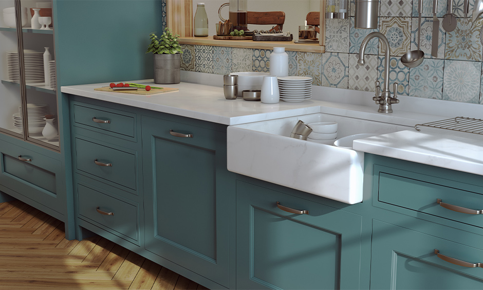 White marble farmhouse kitchen sink with cabinets below in green colour looks elegant.