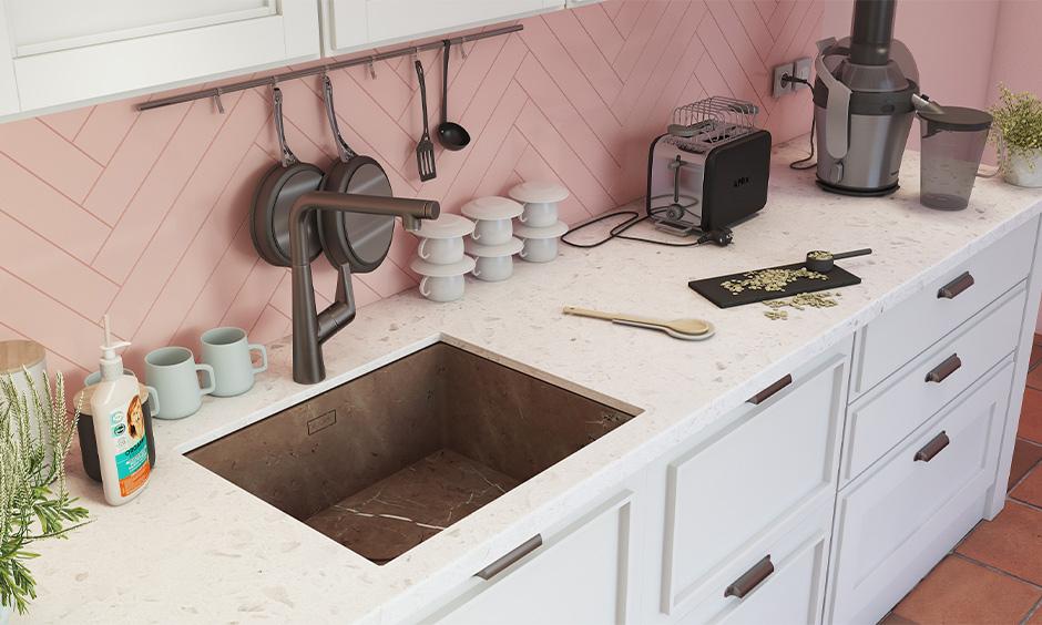 Undermount brown marble kitchen sink design with a white stone countertop looks charming against pink kitchen backsplash.