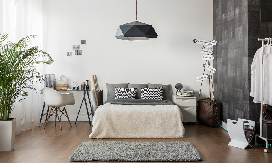 Grey and white bedroom colour combination designed with fancy hanging light, wooden flooring, and study table classic look.