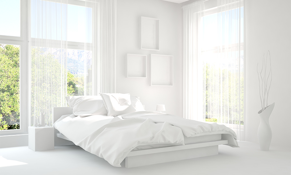 An all-white bedroom has two big windows with transparent curtains and a white vase salubrious look, white bedroom ideas.