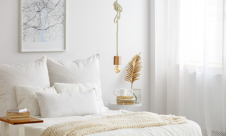 All-white bedroom with a rope hanging light in gold above the side table, and the transparent curtain is sleek.