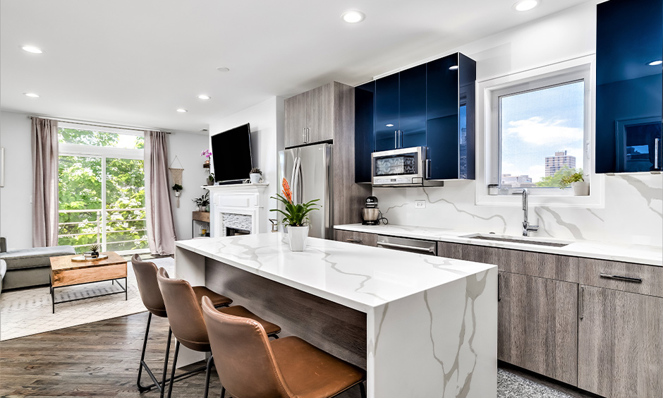 Greyish brown two tone kitchen cabinets and island with a waterfall marble kitchen island