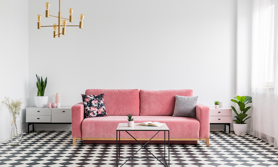 Black and white floor tiles in the room bring a bold look with a pink sofa and hanging light.