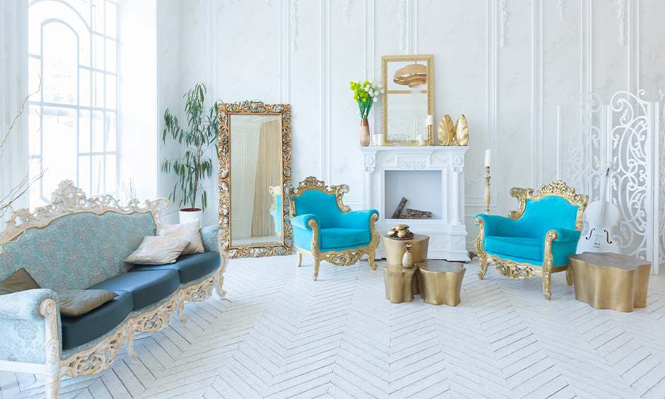 White herringbone tile floor in the white room with ocean blue colour chairs and golden table brings an elegant look.
