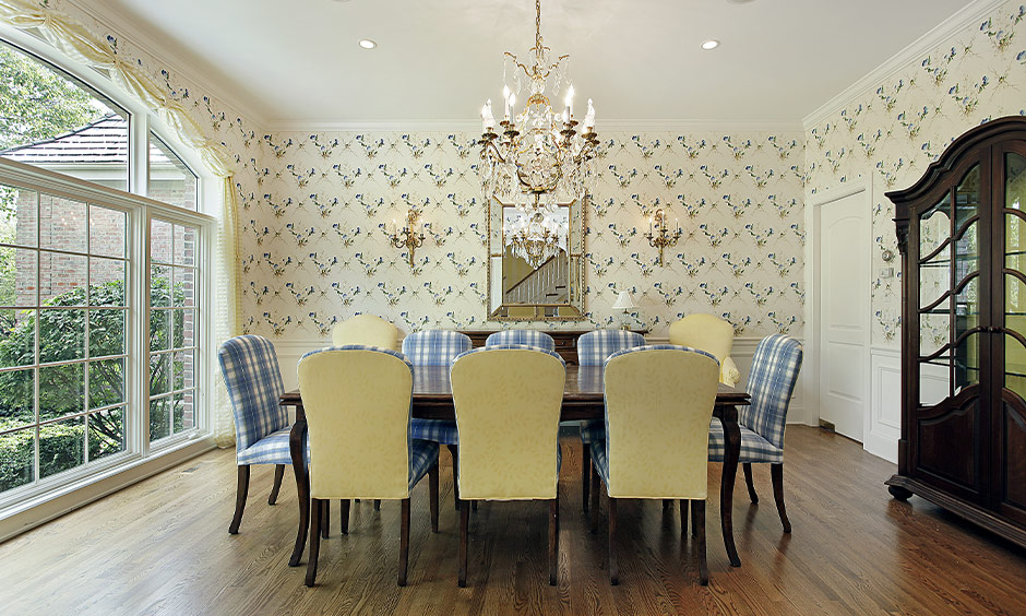 The dining room in pastel yellow and blue combination is a beautiful colour combination for home with chandelier.