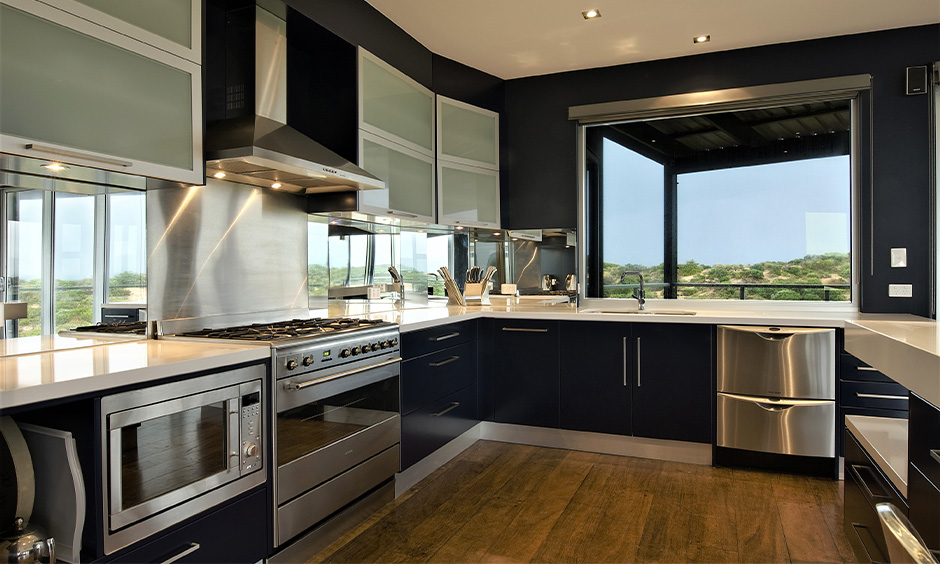Modular stainless steel kitchen cabinets which gives a sleek look to this u-shaped kitchen
