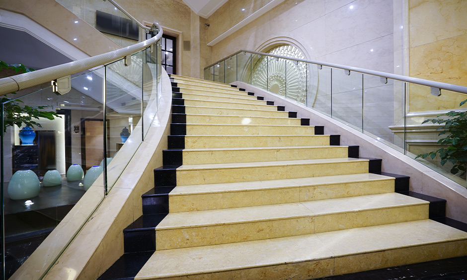 Dual-tone stair marble design in yellow and black with glass railing looks modern.