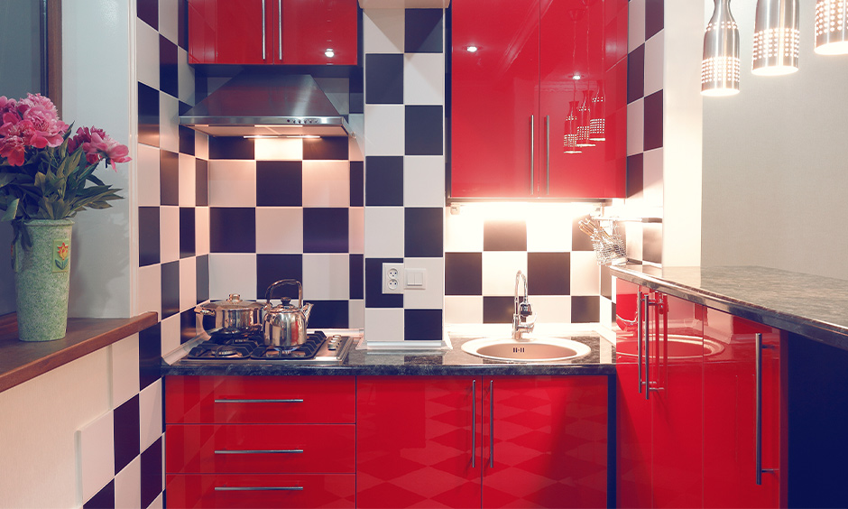 Small kitchen with hanging lights, red cabinets and backsplash look bold is the Indian style kitchen design for small space.