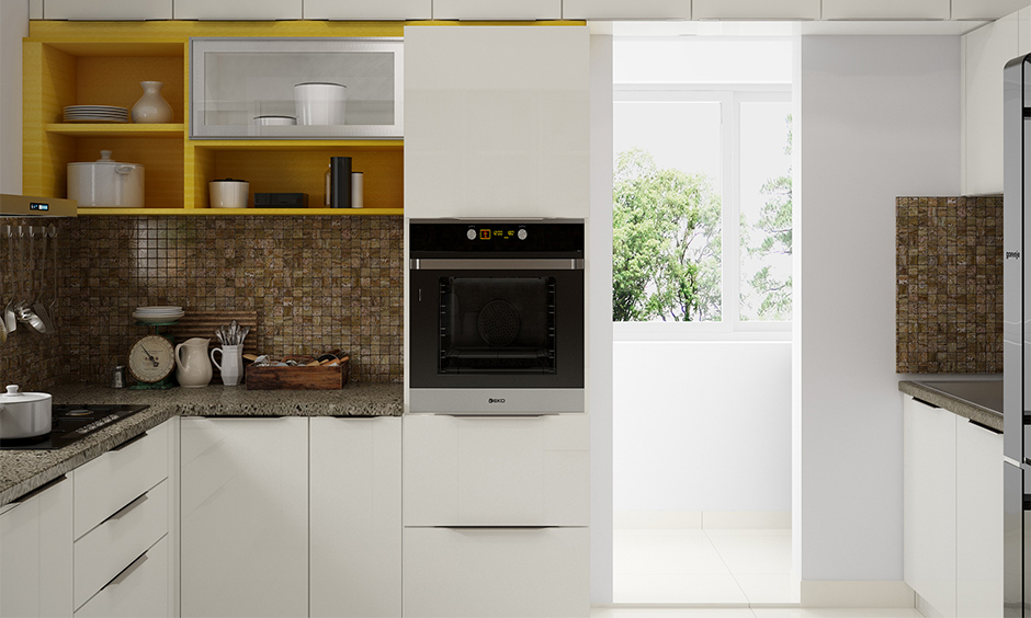 Indian style small modular kitchen design with white cabinets, yellow shelf and brown backsplash looks vibrant.