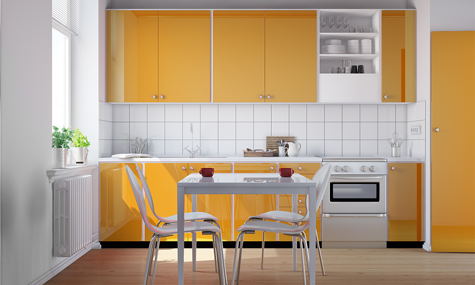 Simple small kitchen design in Indian style with orange cabinets and white dining table looks chic.