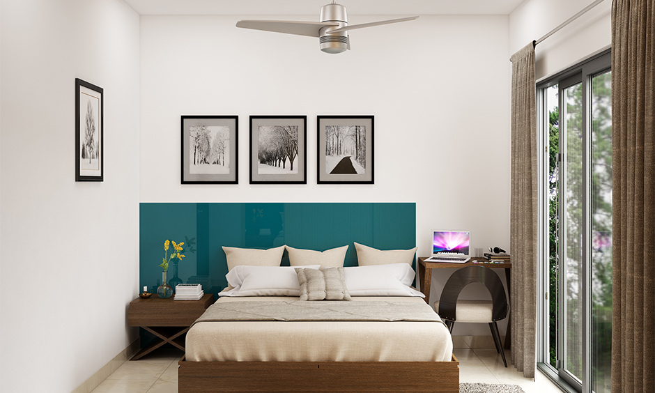 Wooden headboard design in ocean blue colour and glossy finish in the white bedroom looks bold.