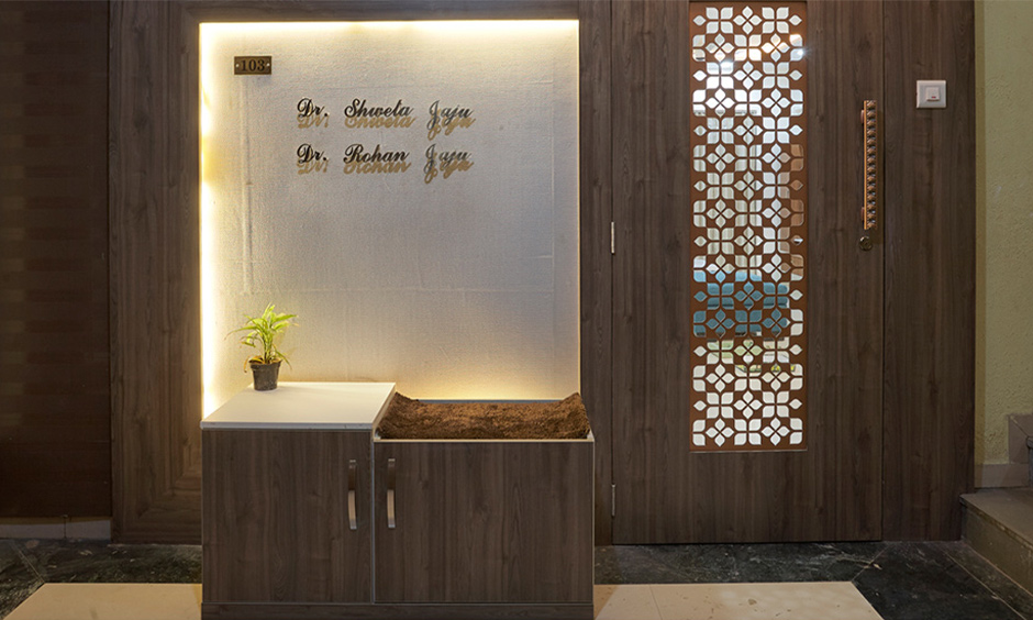 Foyer interior design in Mumbai at kalyan designed in wood with backlighting and a jali door brings  traditional touch.
