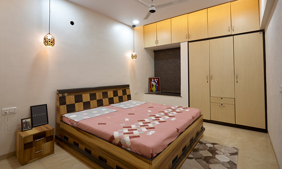 Guest bedroom with wooden wardrobe and hanging lights elegant design, Dc interior designer for Atmosphere Wadhwa.