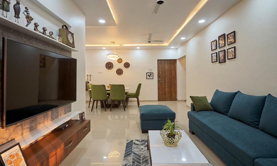 3bhk white living cum dining area design in kalyan city mumbai with tv unit, false ceiling and sofa.