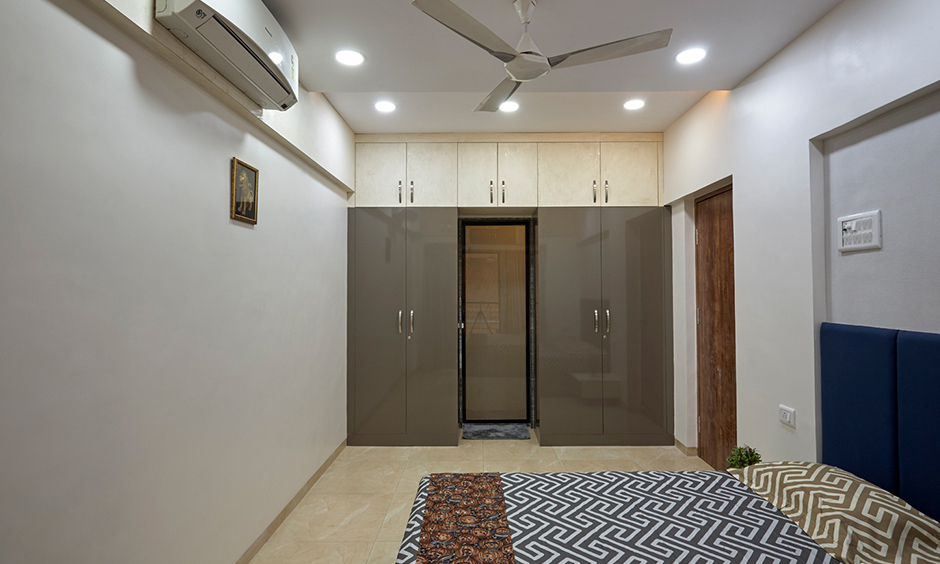 Master bedroom designed by a top interior designer in Mumbai Kalyan City with false ceiling and wardrobe in a glossy finish.