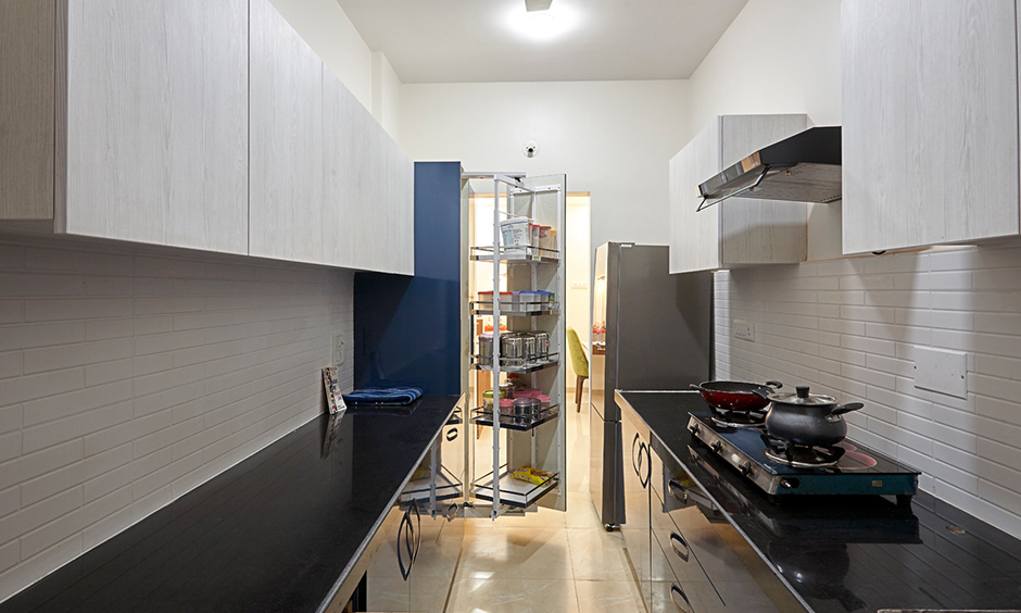 A small parallel kitchen with tall pantry unit looks minimal designed by 3bhk DC residential interior designer in Mumbai Kalyan City.