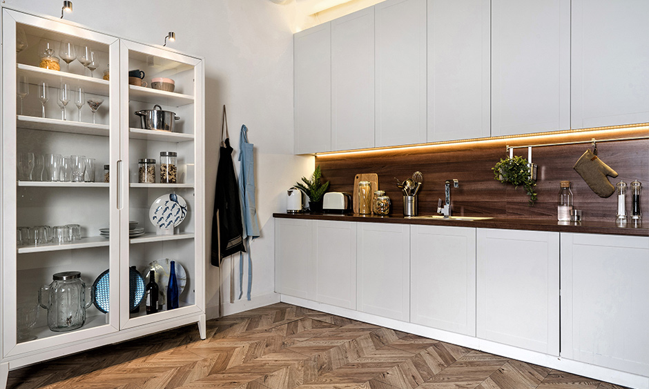 One-wall kitchen with freestanding crockery unit design in wood and glass is the crockery cabinet design for kitchen.