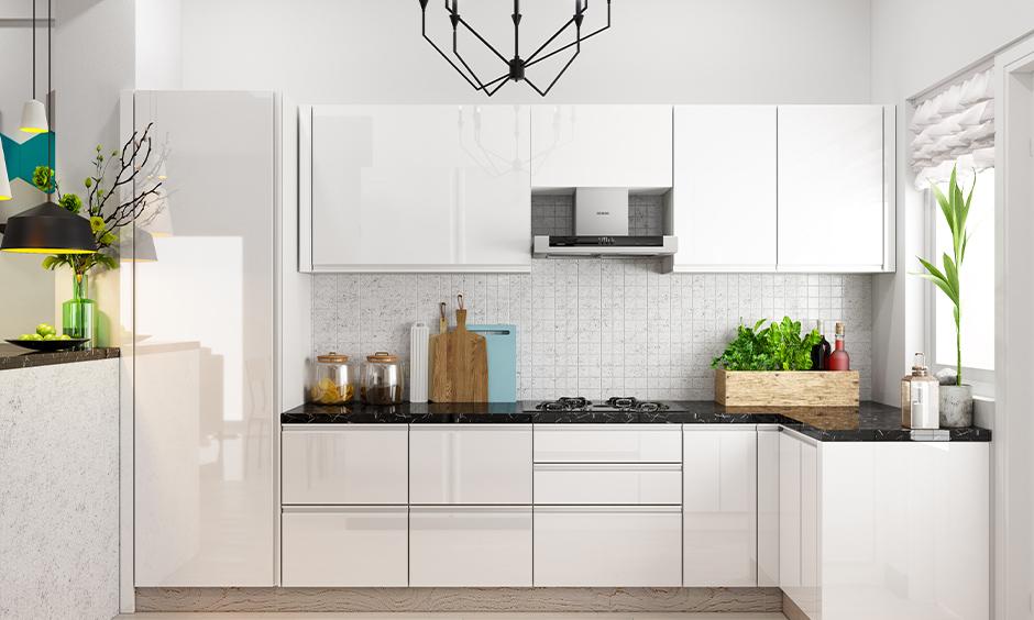 White Indian small kitchen furniture design in a minimalistic and white textured backsplash looks elegant.