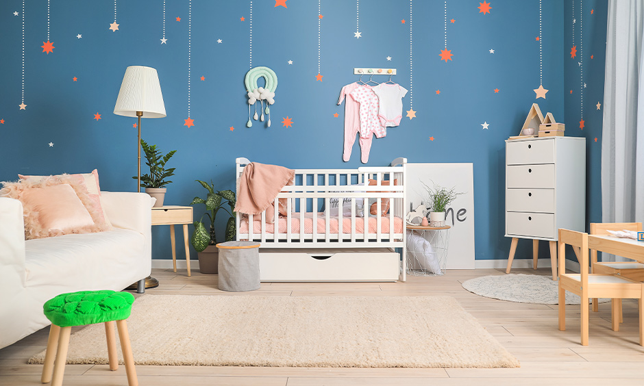 The room wall decorated with star wallpapers in blue colour is the best baby girl room decor idea.