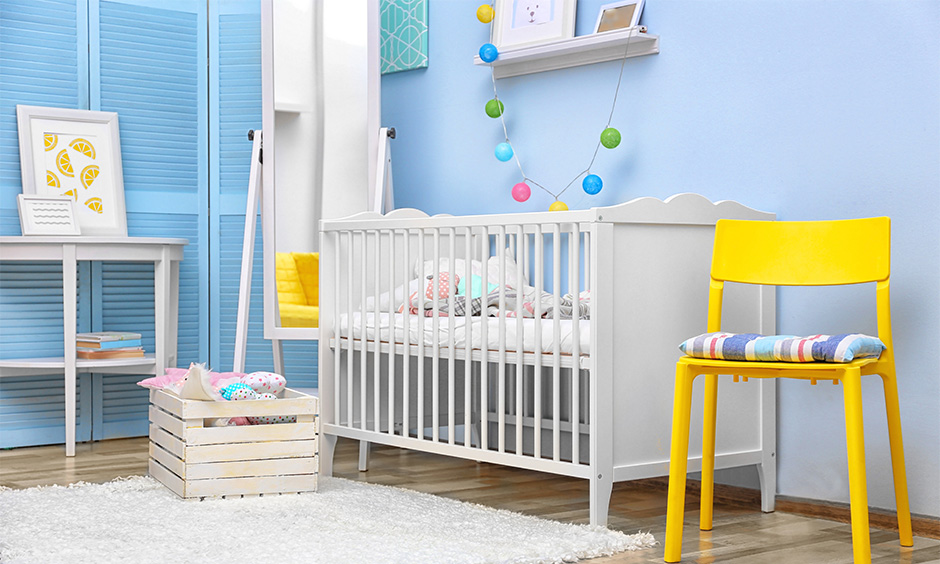 Baby room decorated with a white crib uplifting the colour against blue walls.
