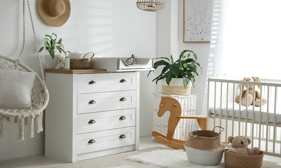 Newborn baby room decoration, the all-white room has a chest of drawers in minimalist design for storage.