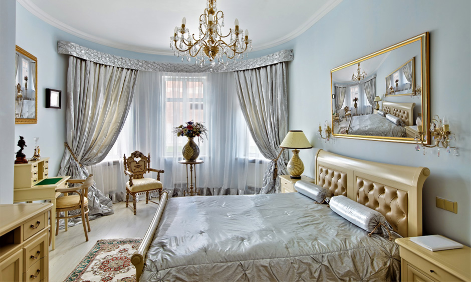 French country interior design bedroom in soft blue color with fancy drapes, study table, and chandelier brings airy vibe.