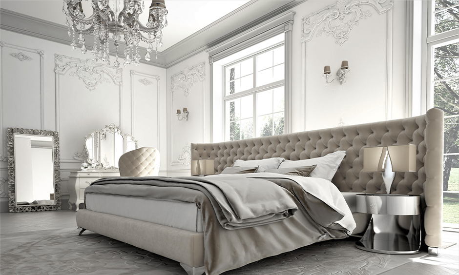 Modern french interior design bedroom in an off-white color with vintage dressing table and chandelier look sleek.